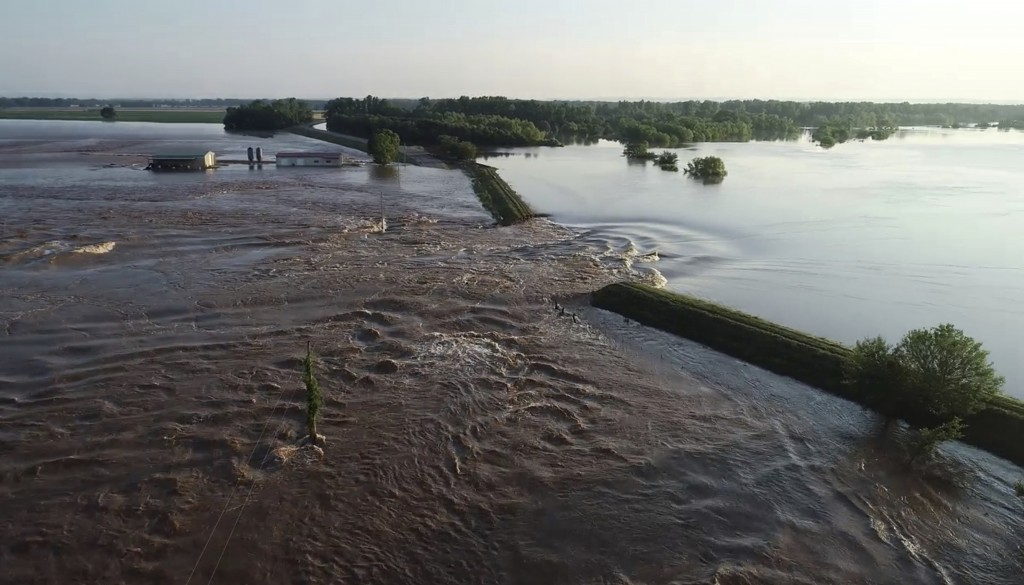 In this aerial image provided by Yell County Sheriff's Department water rushes through the levee along Arkansas River in Dardanelle, Ark., on Friday, ...