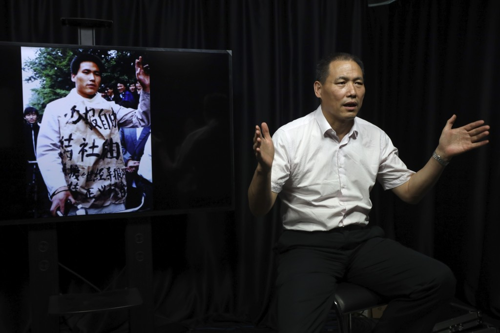 In this May 22, 2019, photo, Pu Zhiqiang recalls his experience near a photo which showed him taking part in the 1989 pro-democracy protest during an ...