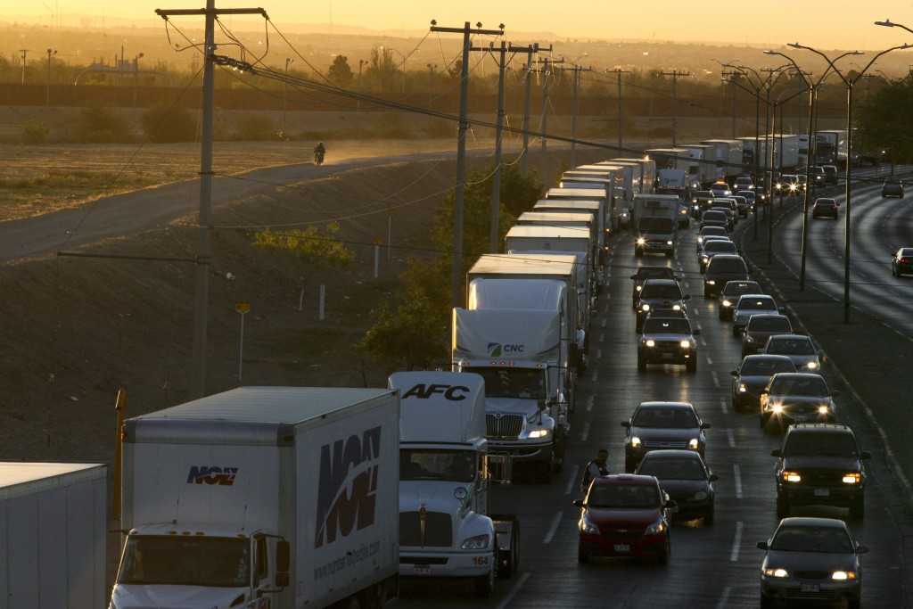 FILE- In this April 9, 2019, file photo, trucks wait to cross the border with the U.S. in Ciudad Juarez, Mexico.  In a surprise announcement that coul