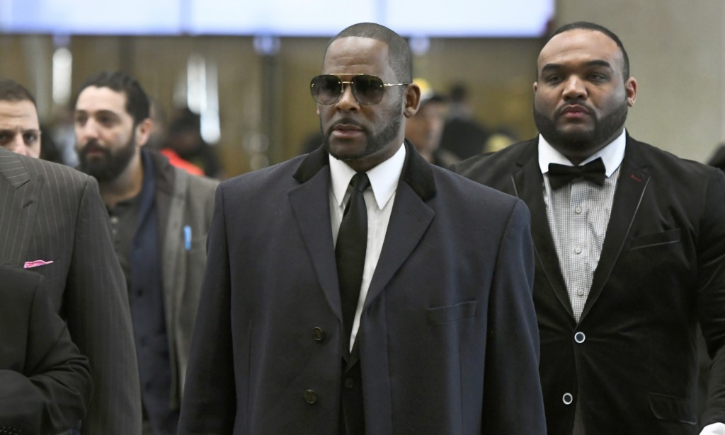FILE - In this May 7, 2019 file photo, Musician R. Kelly, center, arrives at the Leighton Criminal Court building for a hearing in Chicago. Prosecutor...