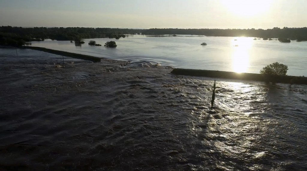 In this aerial image provided by Yell County Sheriff's Department water rushes through the levee along the Arkansas River in Dardanelle, Ark., on Frid...