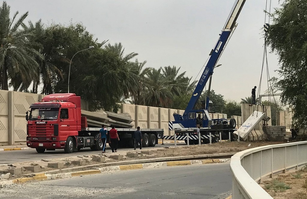In this Tuesday, May 28, 2019 photo, Iraqi security forces remove concrete blast walls at the Green Zone in Baghdad, Iraq. The Green Zone has been a b