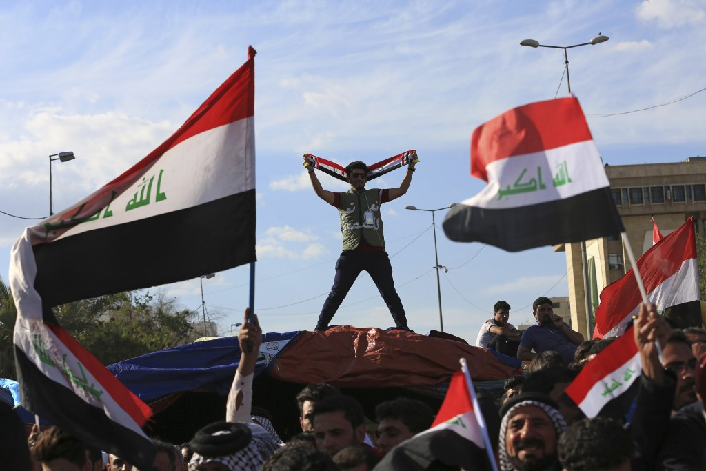 FILE - In this March 31, 2016 file photo, followers of Shiite cleric Muqtada al-Sadr wave national flags as they end their sit-in outside the heavily
