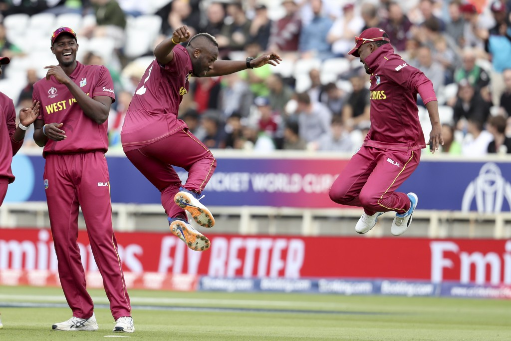 West Indies' bowler Andre Russell, second from right, celebrates with Darren Bravo taking the wicket of Pakistan's Haris Sohail as West Indies' captai...