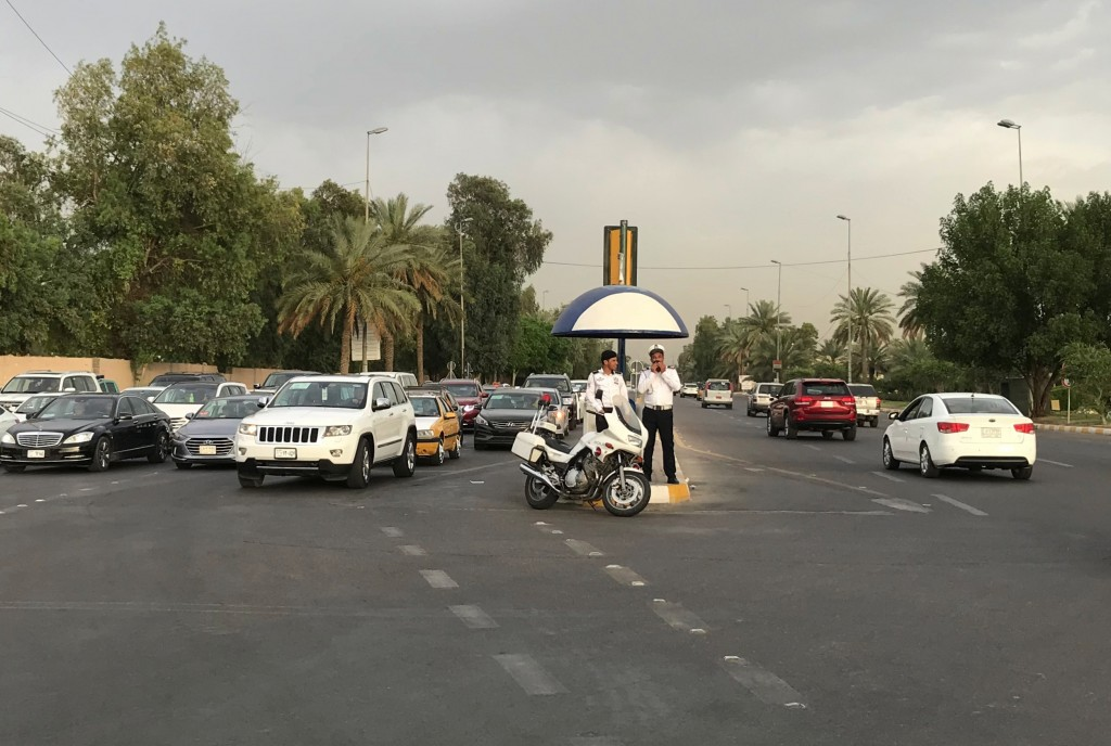 In this Tuesday, May 28, 2019 photo, Iraqi traffic police officers stand at a busy intersection inside the Green Zone in Baghdad, Iraq. The zone has b