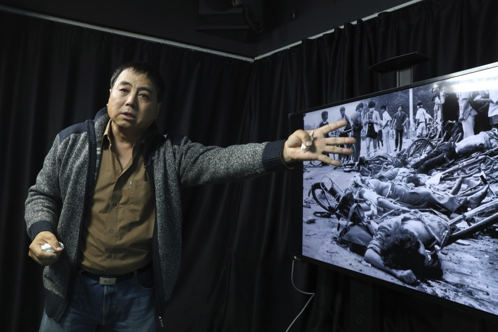 In this April 28, 2019, photo, Dong Shengkun gestures as he recalls being present at the scene seen in the photo when tanks ran down students taking p...