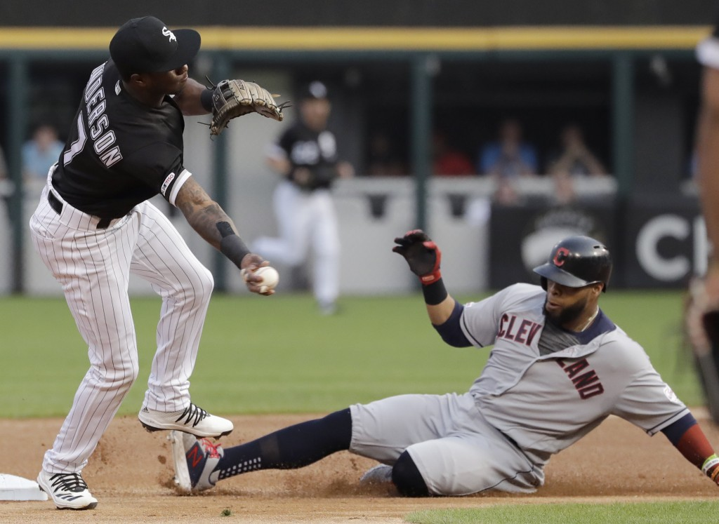Chicago White Sox shortstop Tim Anderson, left, throws to first after forcing out Cleveland Indians' Carlos Santana, right,at second during the first