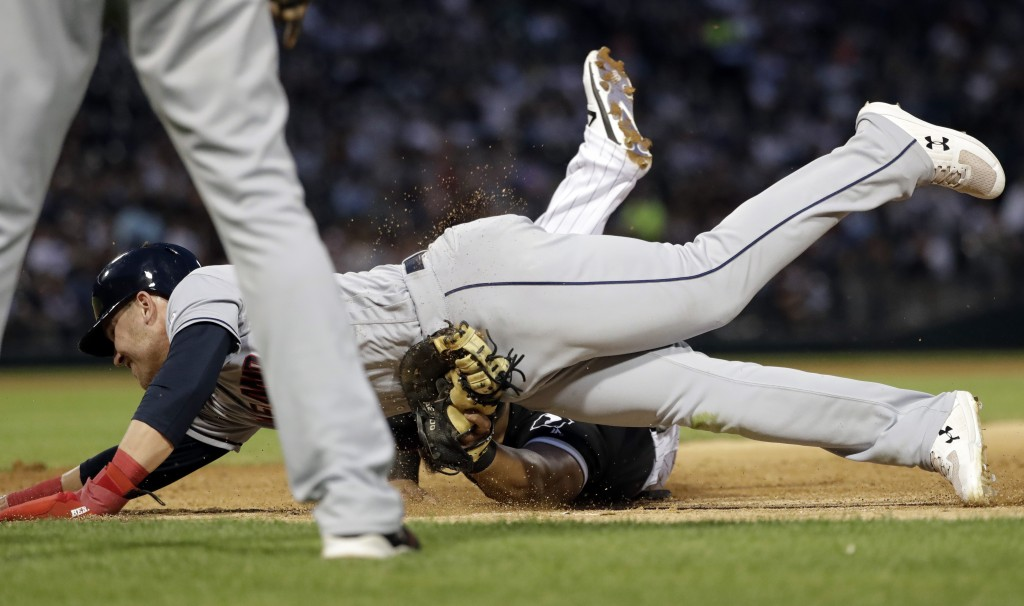 Chicago White Sox first baseman Jose Abreu, bottom, tags out Cleveland Indians' Jake Bauers at first during the fourth inning of a baseball game in Ch...