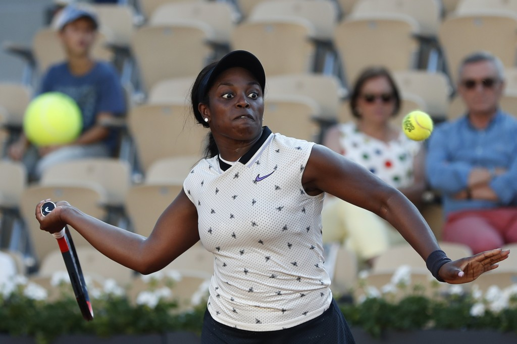 A person in the stands holds a large tennis ball as Sloane Stephens of the U.S. eyes the ball as she plays a shot against Slovenia's Polona Hercog dur
