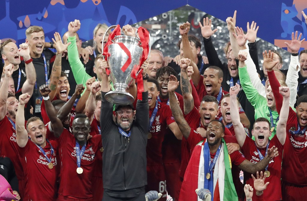 Liverpool coach Juergen Klopp lifts up the trophy as he celebrates with players after winning the Champions League final soccer match between Tottenha