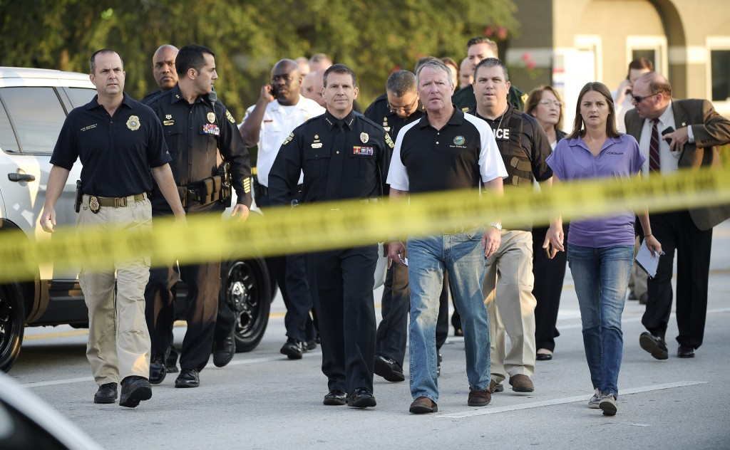FILE - In this Sunday, June 12, 2016 file photo, Mayor Buddy Dyer, center right, and then-Police Chief John Mina, center left, arrive for a news confe...