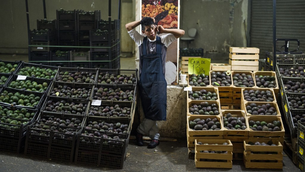 FILE - In this Aug. 9, 2016 file photo, an avocado vendor talks on his cellphone at a market in Mexico City.  Summary: The potential Trump tariffs are...