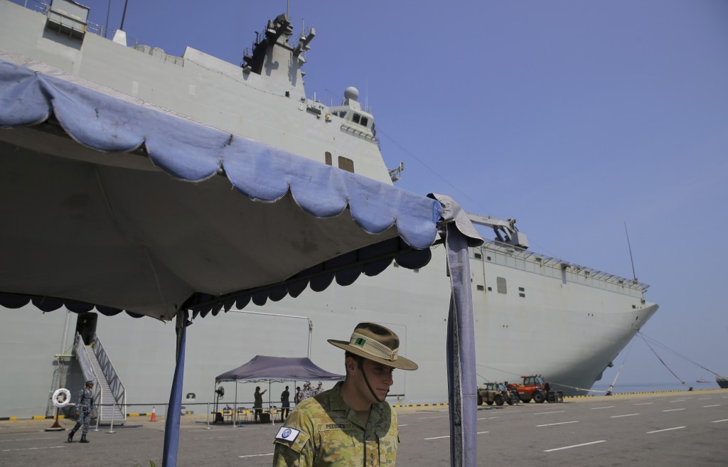 FILE - In this March 29, 2019, file photo, an Australian army officer stands next to the HMAS Canberra, one of four Royal Australian Navy ships visiti...