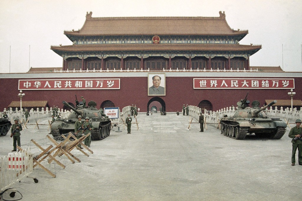 FILE - In this June 10, 1989 file photo, People's Liberation Army (PLA) troops stand guard with tanks in front of Tiananmen Square after crushing the ...