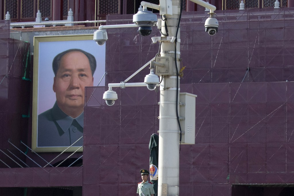 In this May 31, 2019, photo, a Chinese paramilitary policeman stands guard near surveillance cameras in front of Mao Zedong's portrait on Tiananmen Ga...