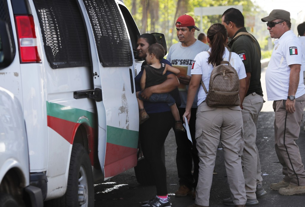 A Central American migrant woman carries her son into van as Mexican immigration officials take them and her other child, not in picture, into custody...