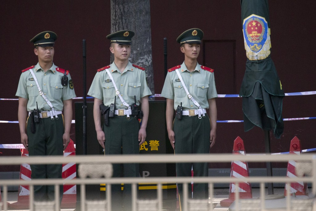 In this May 31, 2019, photo, Chinese paramilitary policemen stand on duty along a avenue near Tiananmen Square in Beijing. Critics say the 1989 Tianan...