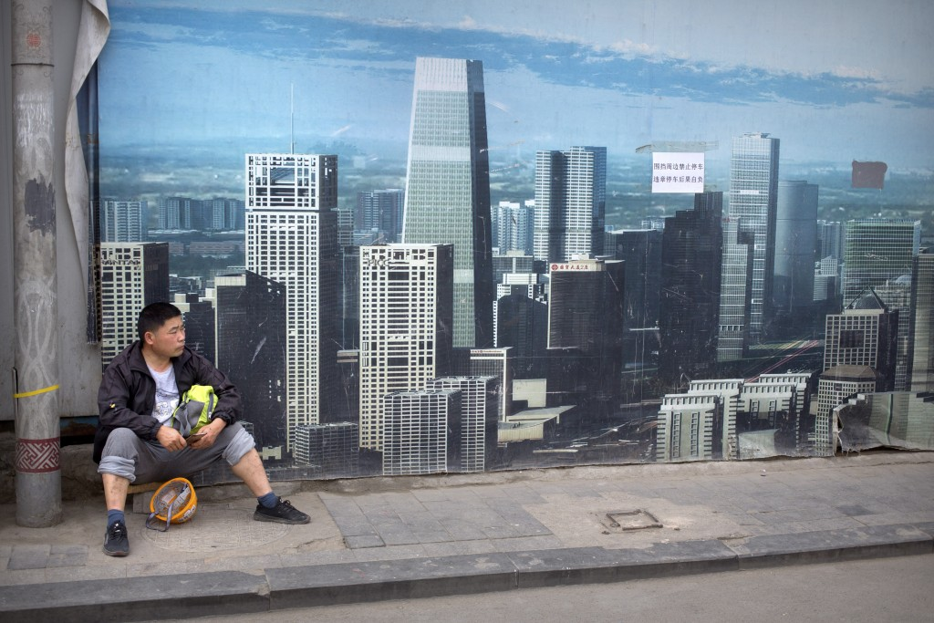 FILE - In this May 16, 2019, file photo, a worker sits in front of a billboard at a construction site in Beijing. Thirty years since the Tiananmen Squ...