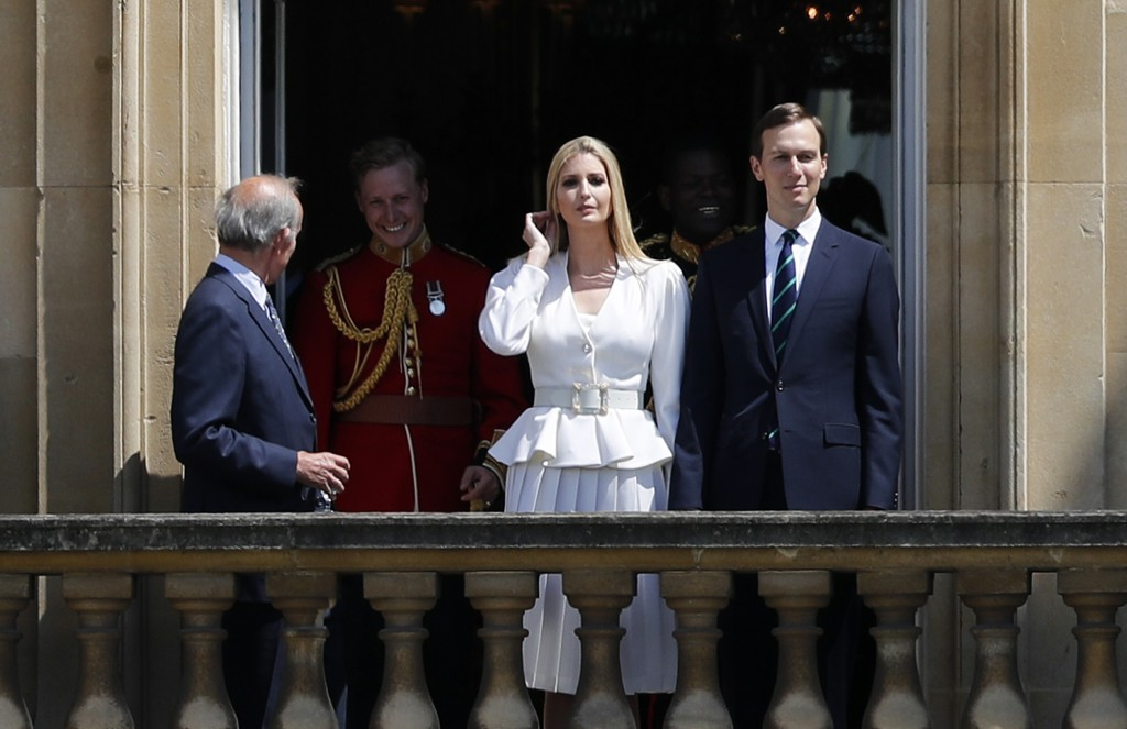 Jared Kushner, right, and Ivanka Trump, second right, watch from a window before a ceremonial welcome in the garden of Buckingham Palace in London for