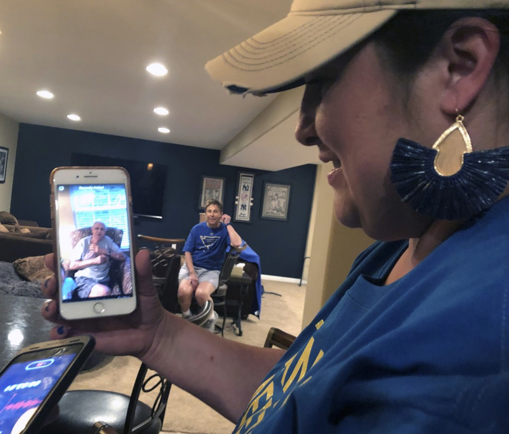Patrick Maroon's sister, Jen Guetschow, holds up her phone to play a video of their late grandfather, Ernest Ferrara, welcoming Maroon back to St. Lou