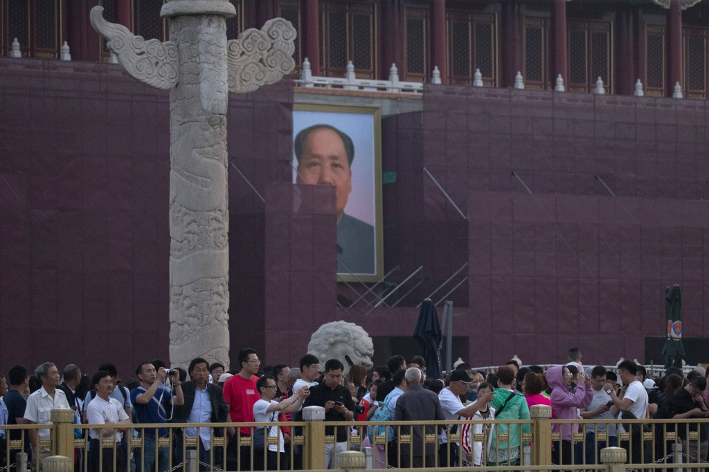 Visitors gather to watch the flag raising in front of Mao Zedong's portrait on Tiananmen Gate on the 30th anniversary of a bloody crackdown of pro-dem...