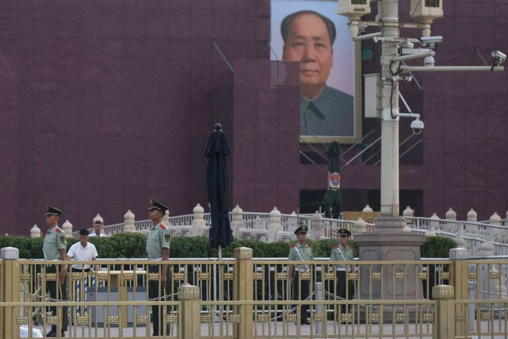 Chinese paramilitary policemen stand guard in front of Mao Zedong's portrait on Tiananmen Gate on the 30th anniversary of a bloody crackdown of pro-de...