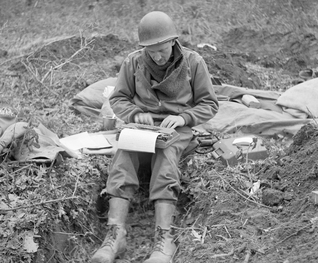 FILE - In this February 1944, file photo, Don Whitehead, Associated Press correspondent, writes his story of the landing at Anzio Beach in Italy, from