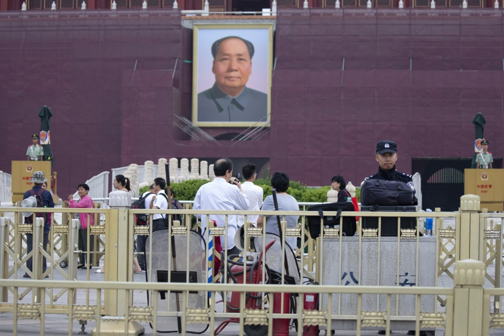 A policeman stands guard near anti-riot gear and fire extinguishers in front of Mao Zedong's portrait on Tiananmen Gate on the 30th anniversary of a b...