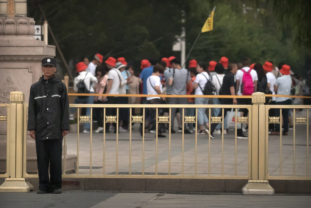 A security official stands guard as a tour group walks along a street next to Tiananmen Square in Beijing, Tuesday, June 4, 2019. Chinese authorities ...