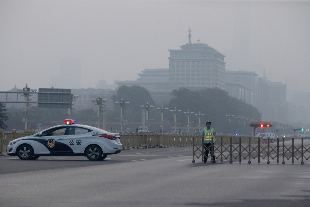 A traffic warden and police vehicle block the road towards Tiananmen Square during flag raising on the 30th anniversary of a bloody crackdown of pro-d...