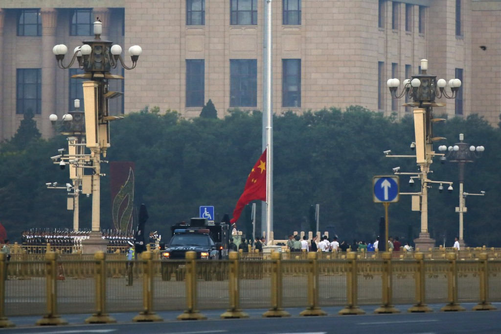 Policemen stand watch as a Chinese honor guard opens the Chinese national flag against the Great Hall of the People during the daily flag raising cere...