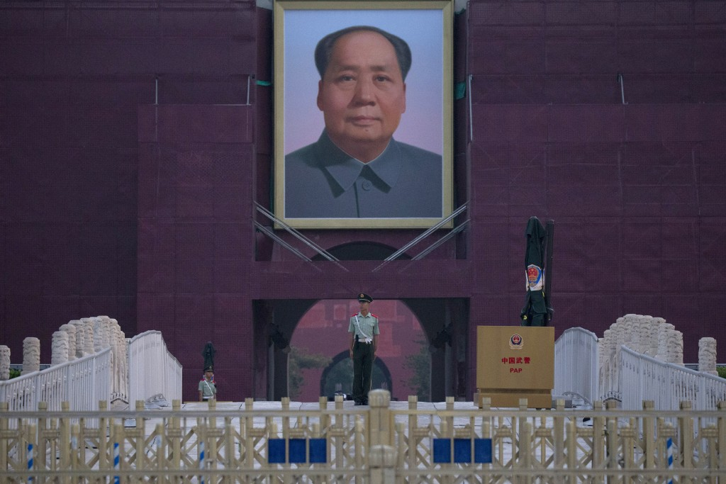 A Chinese paramilitary policeman stands guard in front of Mao Zedong's portrait on Tiananmen Gate on the 30th anniversary of a bloody crackdown of pro...