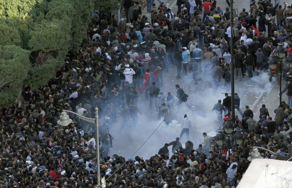 FILE -  In this Jan. 14, 2011, file, photo, demonstrators scatter after police officers use teargas during a protest in Tunis. In the Middle East, it