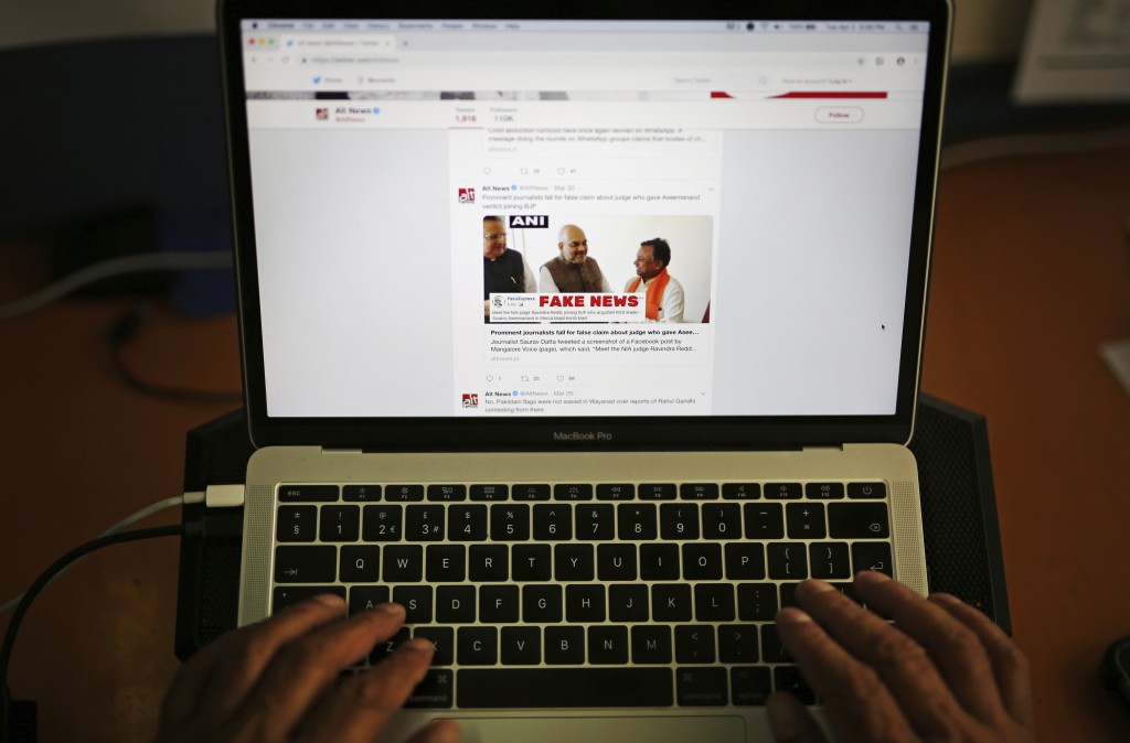FILE - In this Tuesday, April 2, 2019, file photo, a man browses through the Twitter account of Alt News, a fact-checking website. A new survey says h...