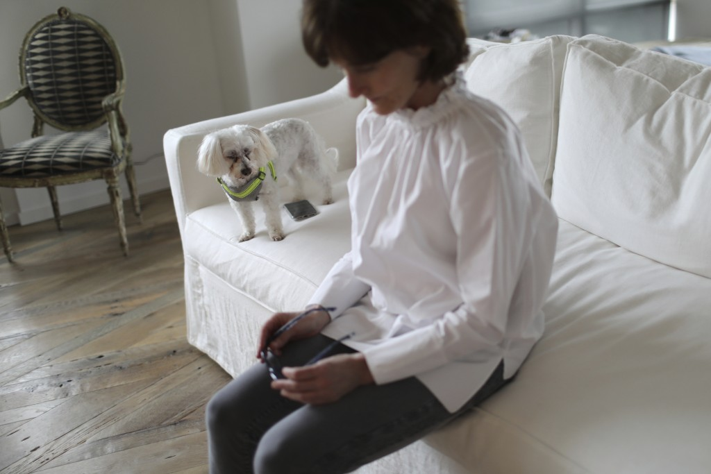 Laura Pontikes holds her eyeglasses while her dog, Coco, watches her in their apartment in Houston on April 13, 2019. Pontikes, a 55-year-old Texas co...