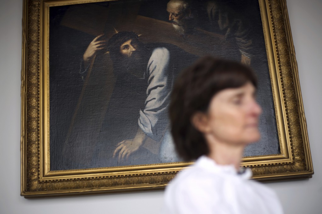 Laura Pontikes closes her eyes while seated in front of an antique oil painting of Jesus during an interview in the prayer section of her apartment in...