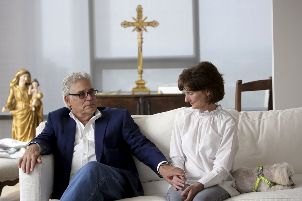 Laura Pontikes pauses as her husband George holds her hand after an interview in their apartment in Houston on April 13, 2019. From beginning to end, ...