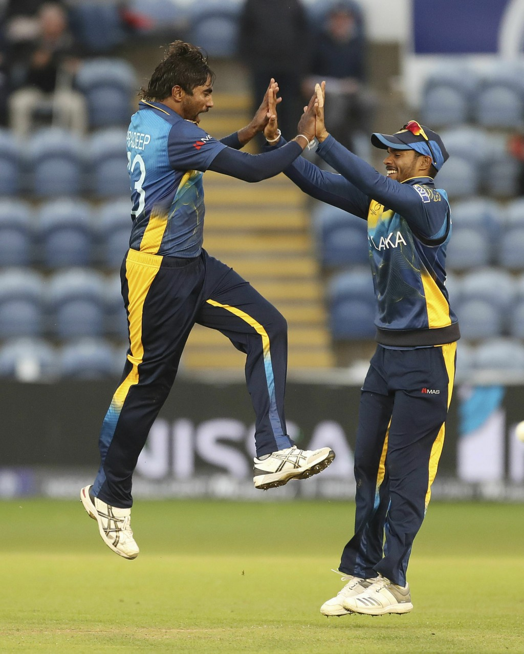 Sri Lanka's Nuwan Pradeep, left, celebrates with Dhananjaya de Silva taking the wicket of Afghanistan's Rashid Khan, during the Cricket World Cup grou