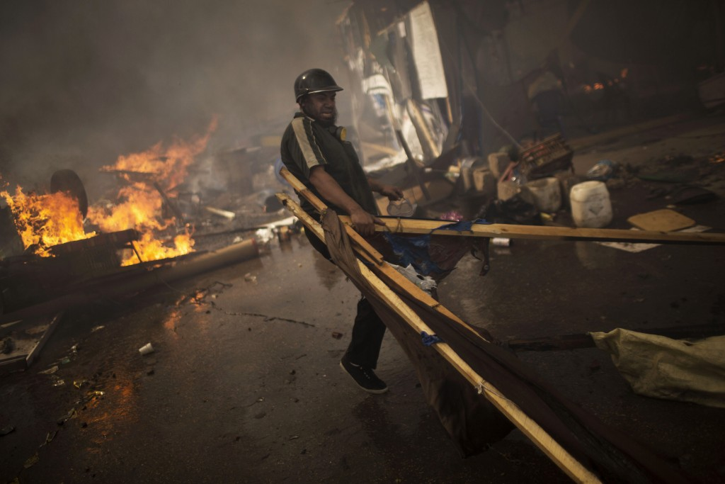 FILE -  In this Aug. 14, 2013, file photo, a supporter of ousted Egyptian President Mohammed Morsi carries wood to burn in a fire barricade at the sit