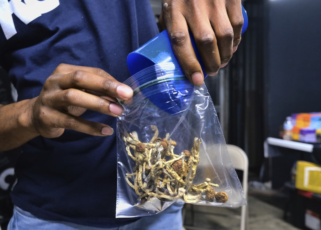 In this Friday, May 24, 2019 photo a vendor bags psilocybin mushrooms at a cannabis marketplace in Los Angeles. Oakland City Council will vote Tuesday...