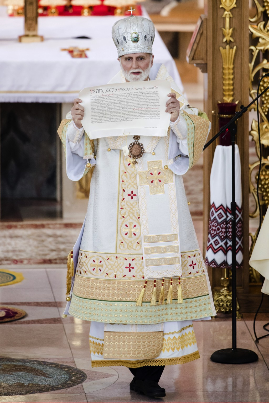 Incoming Metropolitan Archbishop of the Ukrainian Catholic Diocese of Philadelphia Borys Gudziak, displays a document from Pope Francis during a cerem