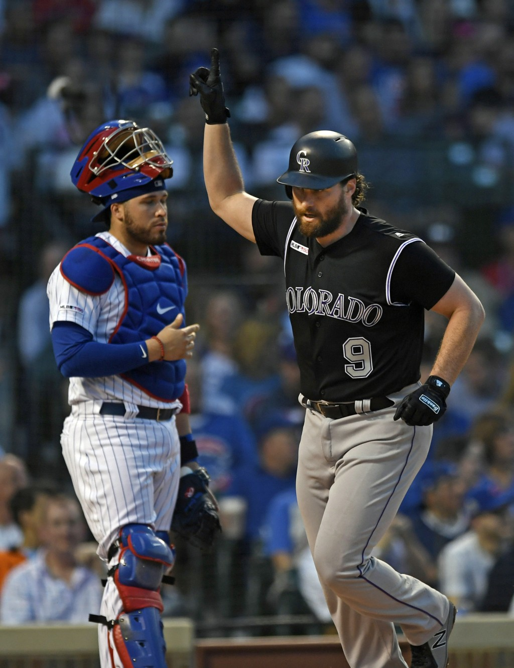 Colorado Rockies' Daniel Murphy right, celebrates at home plate after hitting a solo home run while Chicago Cubs catcher Victor Caratini left, looks o...
