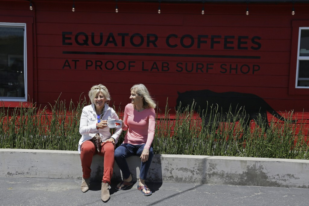 In this Tuesday, June 4, 2019, photo Helen Russell, left, and her partner Brooke McDonnell, co-founders of Equator Coffees, sit outside their first ca