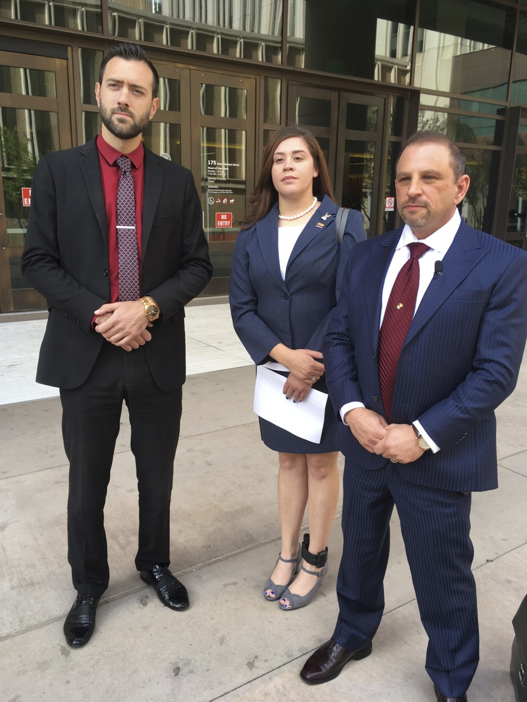 FILE - In this March 29, 2018 file photo, 32-year-old Tahnee Gonzales of Glendale, Arizona, stands next to her attorneys Marc Victor, right, and Andre