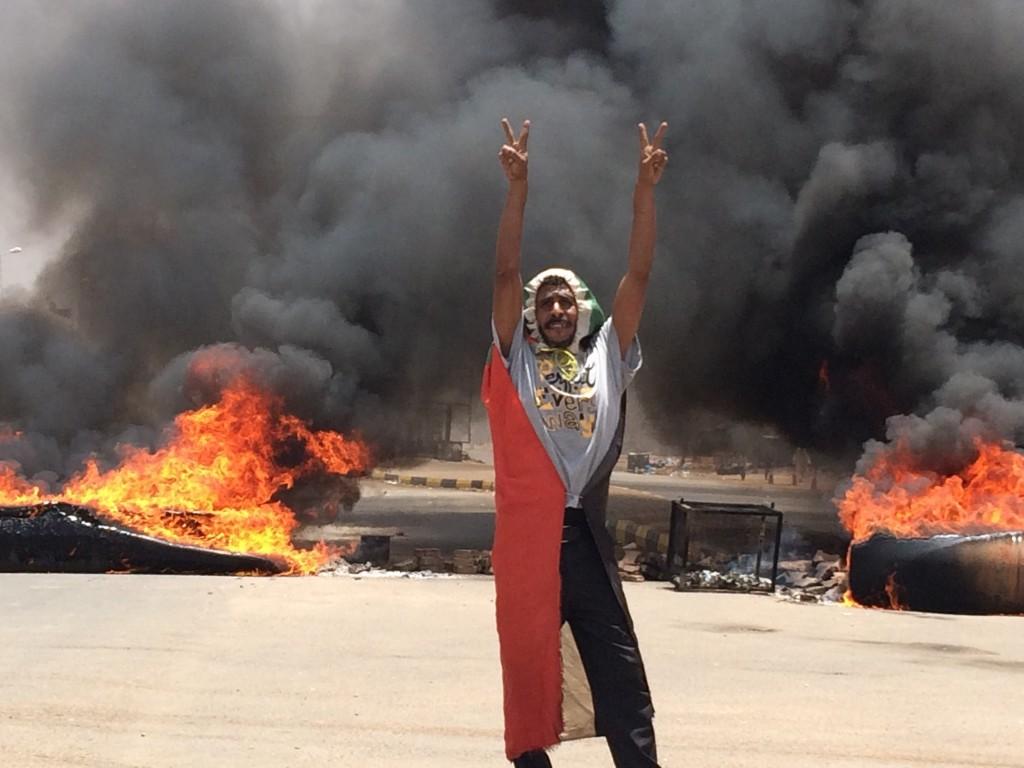 FILE - In this June 3, 2019 file photo, a protester flashes the victory sign in front of burning tires and debris on road 60, near Khartoum's army hea