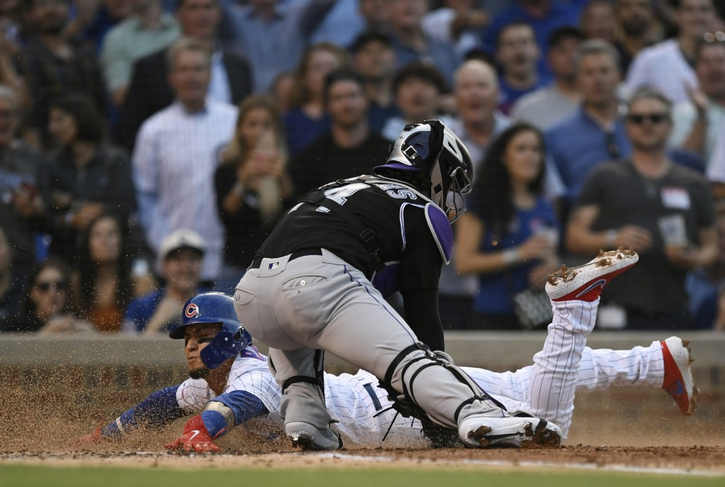 Chicago Cubs' Javier Baez slides into home plate safely on a Carlos Gonzalez double as Colorado Rockies catcher Tony Wolters attempts to apply the tag...