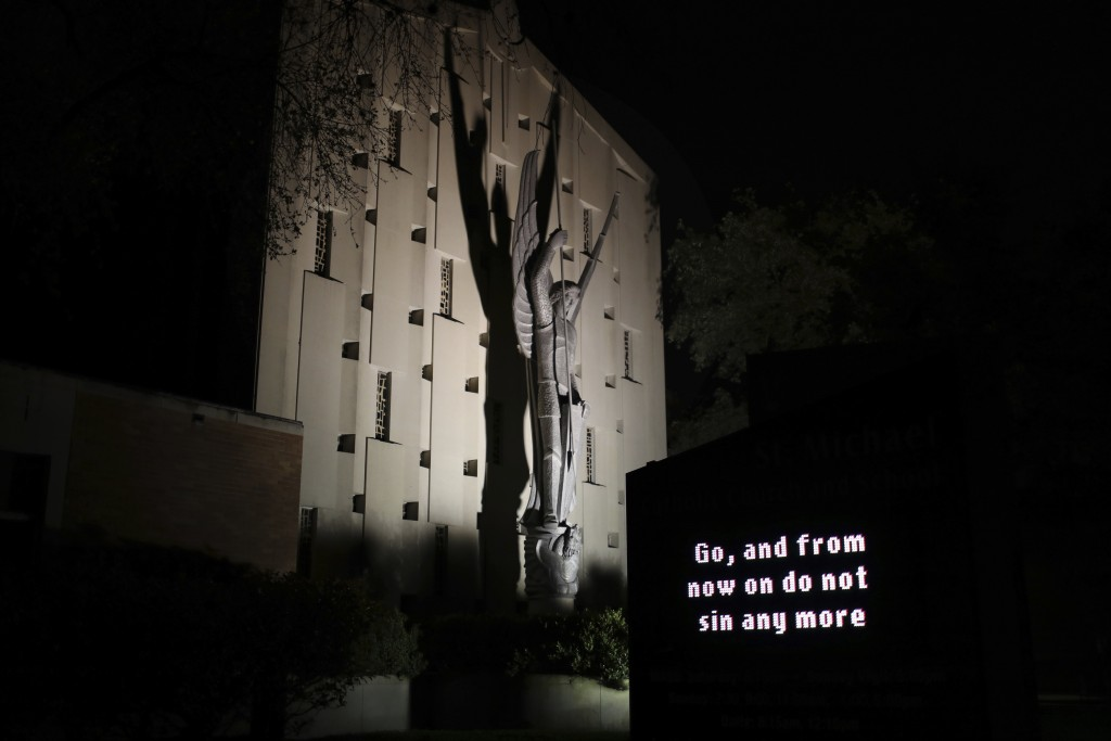 """An illuminated sign outside St. Michael Archangel Catholic Church in Houston reads, """"Go, and from now on do not sin any more"""" on April 11, 2019. The c..."""