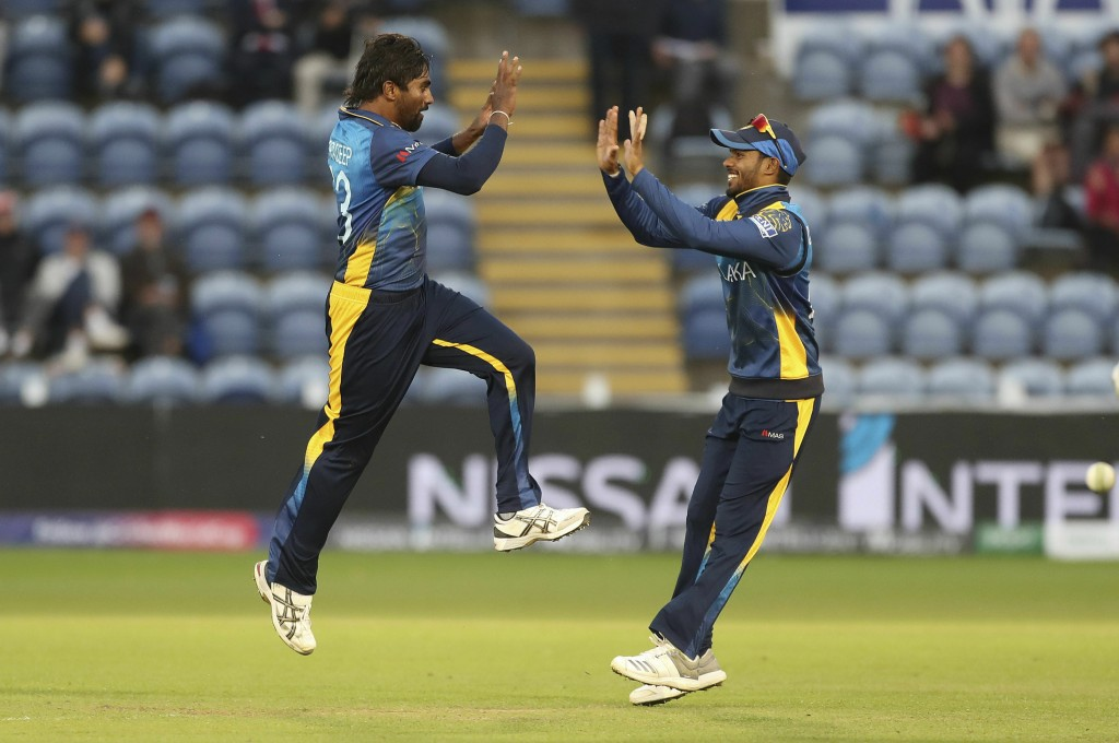 Sri Lanka's Nuwan Pradeep, left, celebrates with Dhananjaya de Silva taking the wicket of Afghanistan's Rashid Khan during the Cricket World Cup group