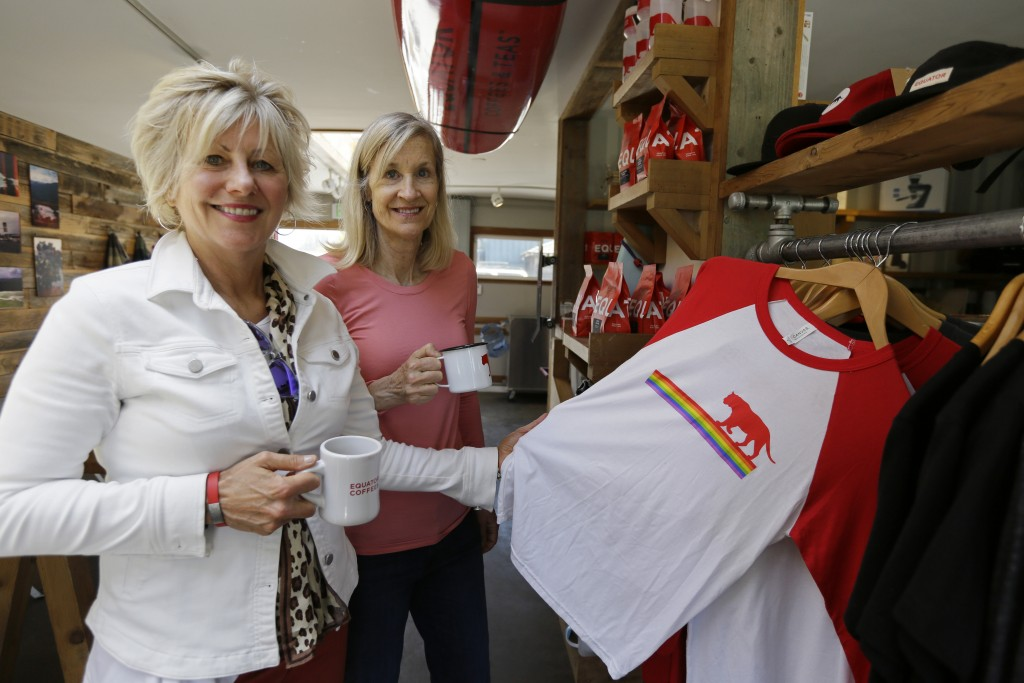 In this Tuesday, June 4, 2019, photo Helen Russell, left, and her partner Brooke McDonnell, co-founders of Equator Coffees, pose with a shirt they sel