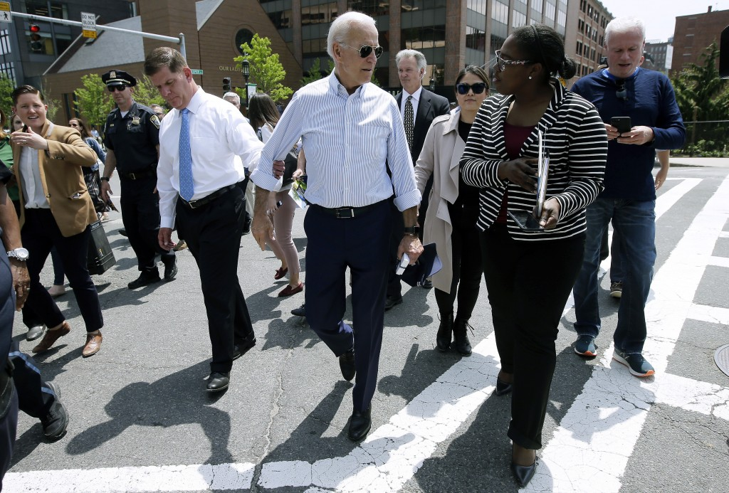 Former vice president and Democratic presidential candidate Joe Biden speaks with a woman as he walks with Boston Mayor Marty Walsh, left, on Wednesda...